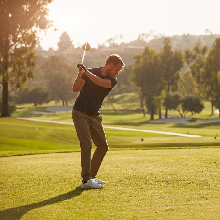 Man playing golf on a beautiful green course